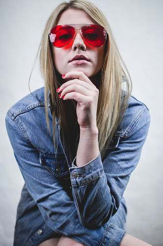 person woman in blue denim jacket wearing red sunglasses and red manicure with hands on chin human