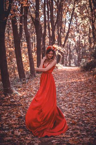 person woman in red dress surrounded by trees human