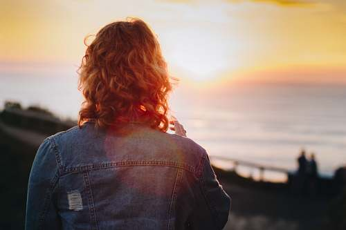 person woman standing in front of ocean during sunset hair
