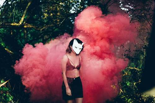 woman woman standing in front of red smoke mask