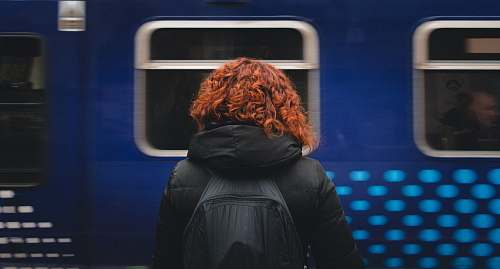 human woman wearing black hooded jacket and black backpack standing in front of moving blue train person