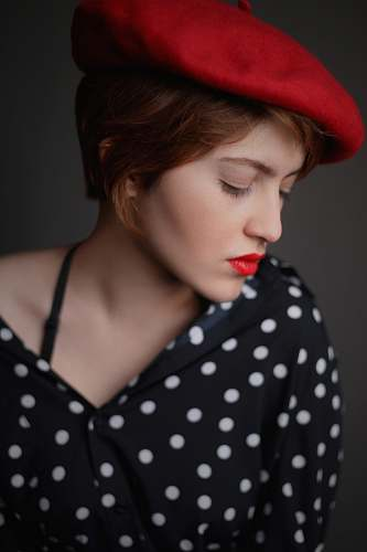 person woman wearing red newsboy hat and black and white polka-dotted button-up top human