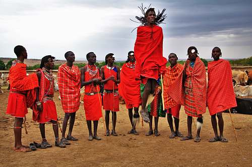 people group of men wearing red suits standing on brown soil tribe