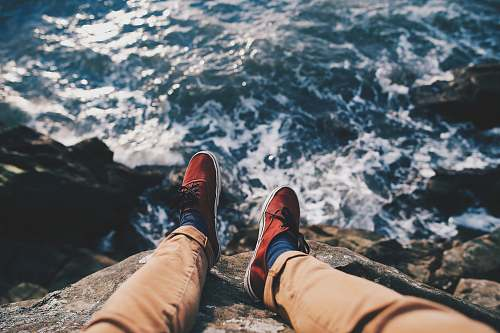 human man in red sneakers sitting in cliff near body of water shoe