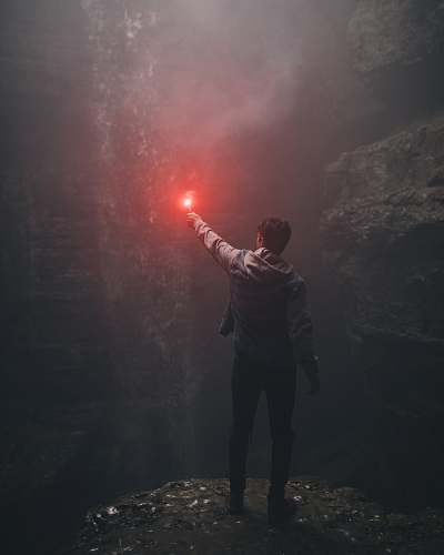 people man lighting up flare in cave human