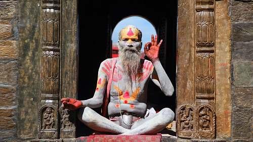 beard man sitting on brown wall people