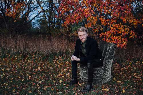 people man wearing black suit sits on black concrete chair beside brown tree human