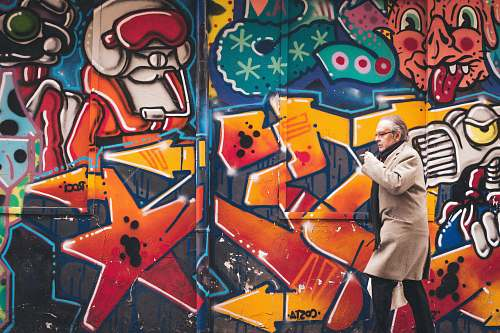 graffiti man wearing grey coat walking beside wall with graffiti human