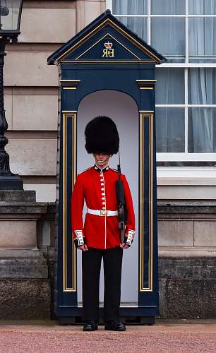 military Royal Guard standing near post military uniform