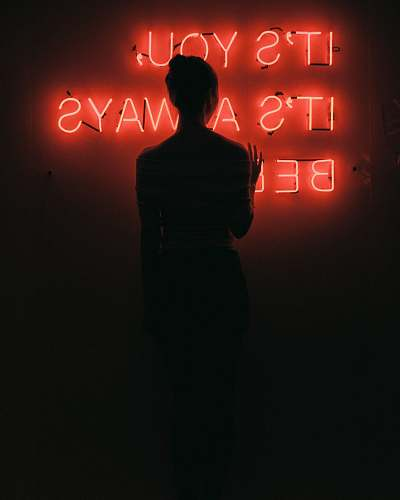 human silhouette of woman standing in front of red neon signage low light photography people