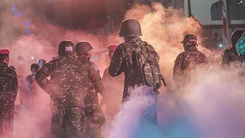 human soldiers against crowd of people with smoke trail people