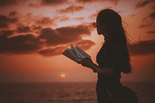 people woman holding book while looking at body of water during golden hour book