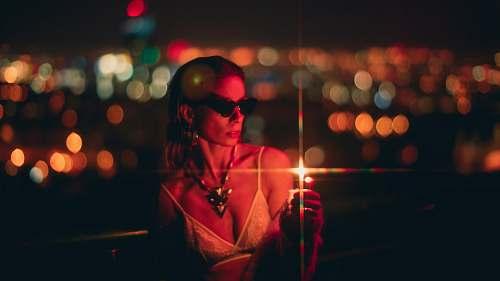 human woman holding lighter at night sunglasses