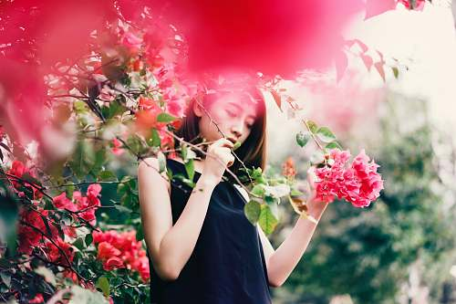 human woman in black sleeveless top holding branch of plants with red flowers people