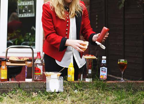photo people woman putting red sauce on hamburger bbq free for commercial use images