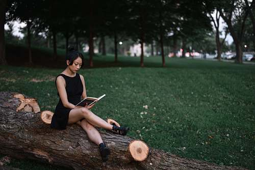 people woman reading book while sitting on fallen tree trunk human