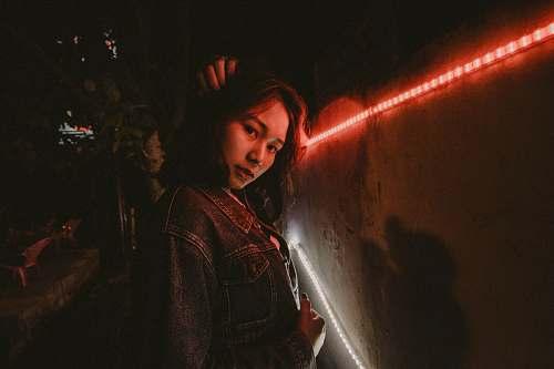 human woman wearing blue denim jacket standing beside red LED people