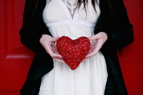 people women holding red heart pillow love