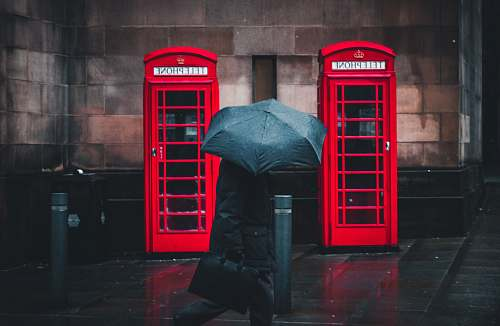 umbrella person under umbrella walking beside telephone booths manchester
