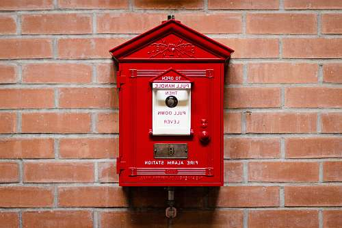 mailbox red fire alarm station attached on brick wall red