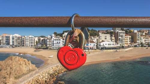 love heart padlock hanging on brown pipe ocean