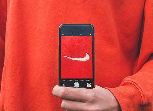 phone person holding iPhone taking picture on Nike label skjød