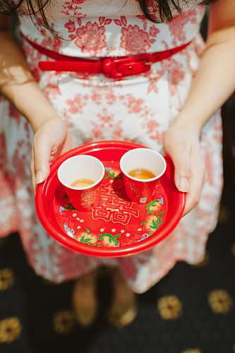 cup person holding plastic plate with two red cups coffee cup