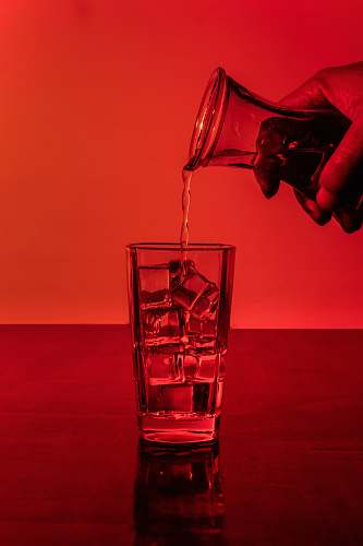 glass person pouring water in glass with ice cubes alcohol