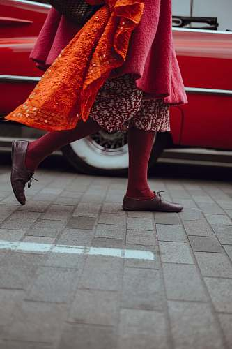 shoe photo of person walking in front of red vehicle walking
