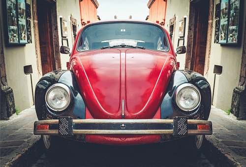 car photo of red and black Volkswagen Beetle in alley vehicle