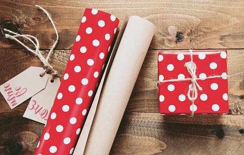 gift red and white polka-dot gift box beside gift wrappers table