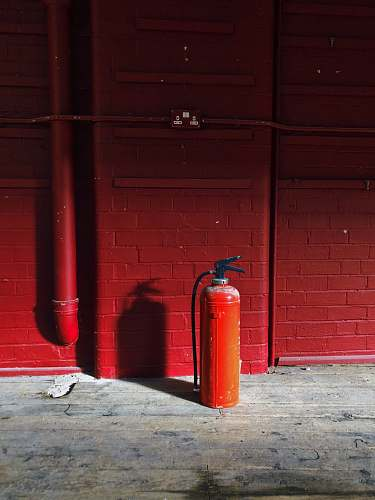brick red fire extinguisher near red wall wall