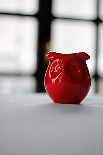 jug red owl figurine on white surface white tablecloth