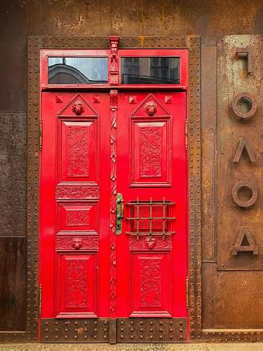 door red painted door on brown rustic metal wall path