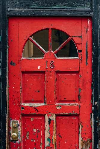 door red wooden door with brass doorknob outdoors
