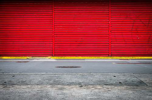asphalt three panels of red roll up doors closed tarmac