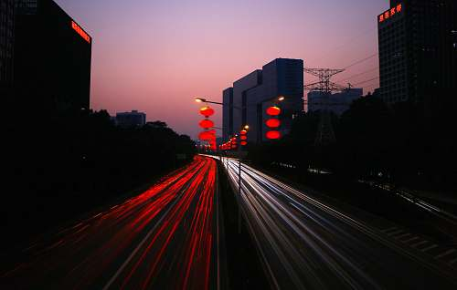 sunset timelapes photography of car lights on road during night time city