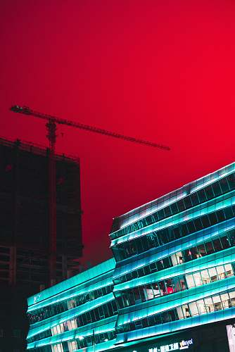 building tower crane between buildings under red sky office building