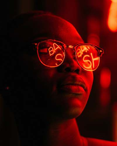 neon woman wearing eyeglasses with red LED signage reflection woman