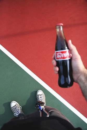 apparel person holding Coca-Cola bottle footwear
