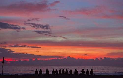 people people sitting on seashore while watching golden hour sunrise
