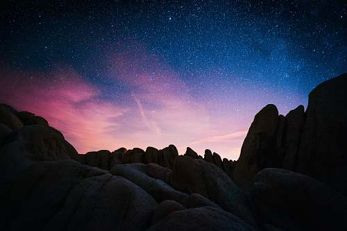 night rock mountain during starry night space