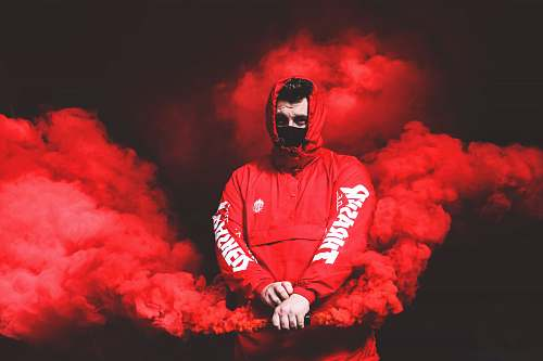 person man in red Thrasher pullover hooded jacket with red smoke human