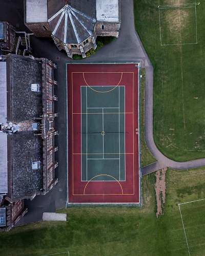 sportsfield aerial photo of green and red sports field tennis court