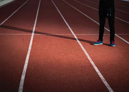 sports person standing on brown and white surface running track