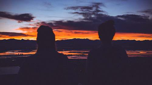 sunset silhouette photo of two women starring at sunset nature