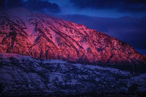sunset snow-covered mountain under cloudy sky during nighttime mountains