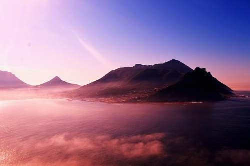 sunrise mountain near body of water under blue sky hout bay