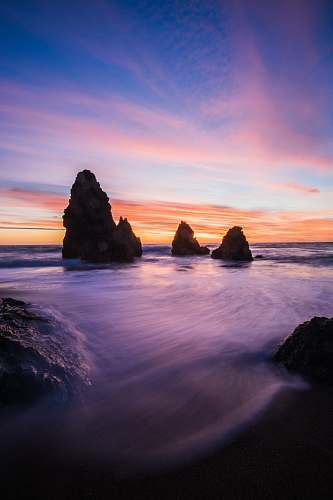 sky rock formations in body of water at blue hour sunrise