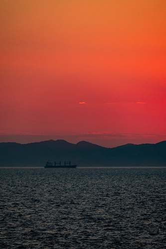 nature sillhoutte photography of ship in the sea during golden hour sky